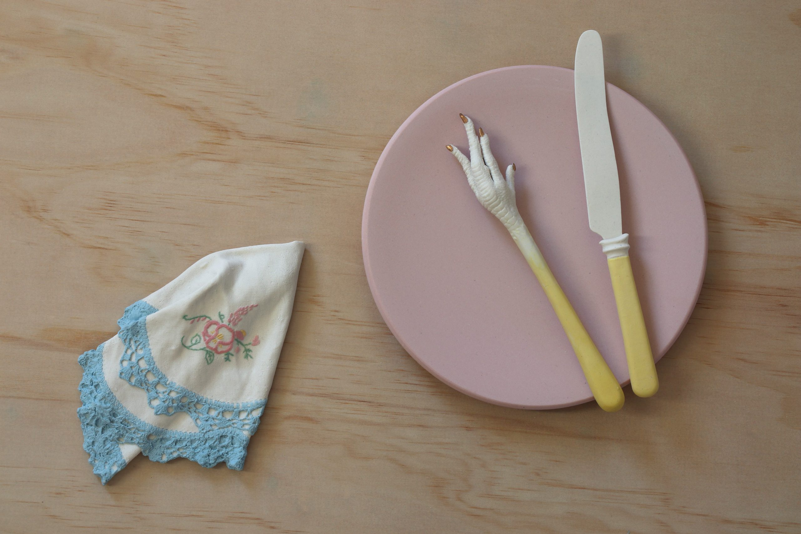 Sculpture with mid century porcelain napkin, chicken foot fork, knife and plate